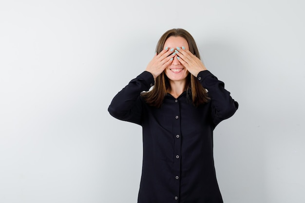 Portrait de jeune femme tenant les mains sur les yeux