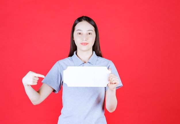 Portrait de jeune femme tenant une planche et pointer du doigt dessus