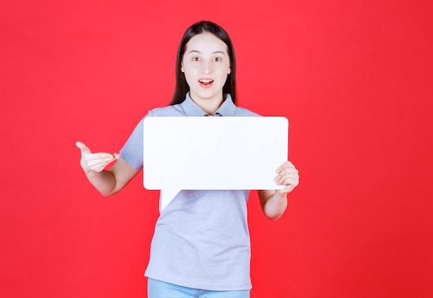 Portrait de jeune femme tenant une planche et pointer la main dessus