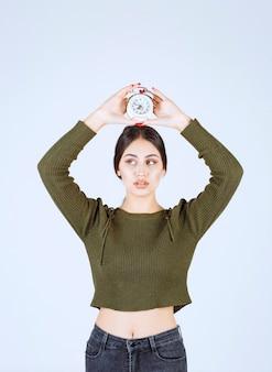 Portrait de jeune femme tenant un réveil avec une expression sérieuse.