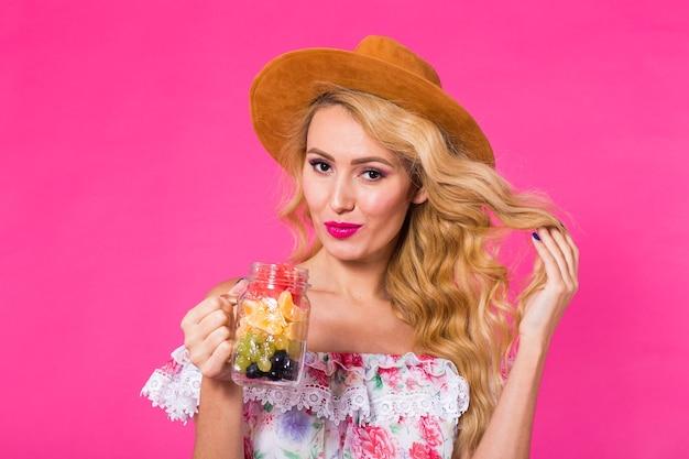 Portrait de jeune femme tenant de savoureux fruits frais en bouteille sur un mur rose.
