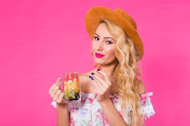 Portrait de jeune femme tenant de savoureux fruits frais en bouteille