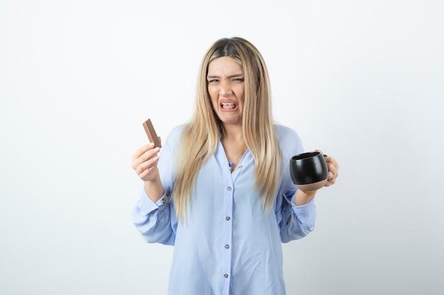 Portrait de jeune femme tenant une tasse de boisson et une barre de chocolat avec dégoût