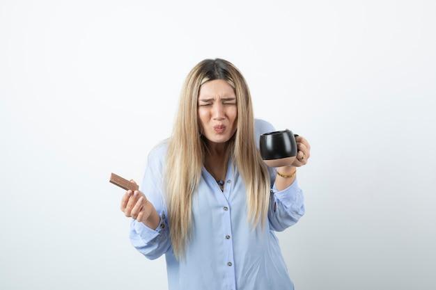Portrait de jeune femme tenant une tasse de boisson chaude avec barre de chocolat