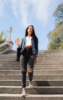 Portrait de jeune femme tenant une tasse de café en marchant à l'extérieur. concept urbain.