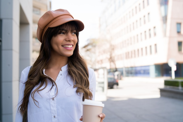 Portrait de jeune femme tenant une tasse de café en marchant à l'extérieur dans la rue. notion urbaine.