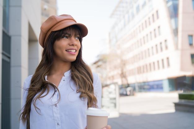 Portrait de jeune femme tenant une tasse de café en marchant à l'extérieur dans la rue