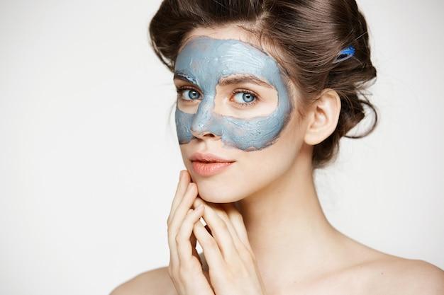 Portrait de jeune femme tendre en bigoudis et masque facial souriant. concept de beauté et de soins de la peau.