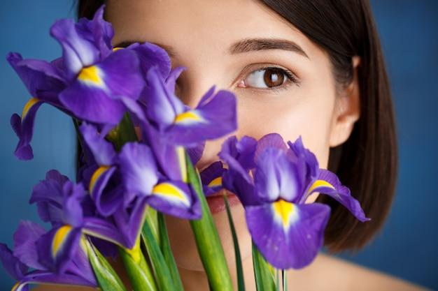Portrait de jeune femme tendre derrière des iris violets sur mur bleu