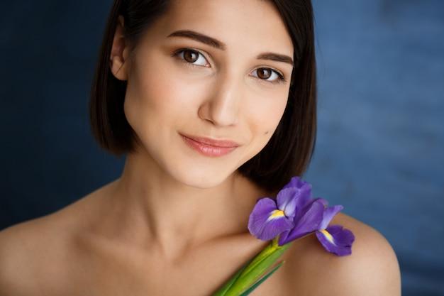 Portrait de jeune femme tendre avec fleur violette sur mur bleu