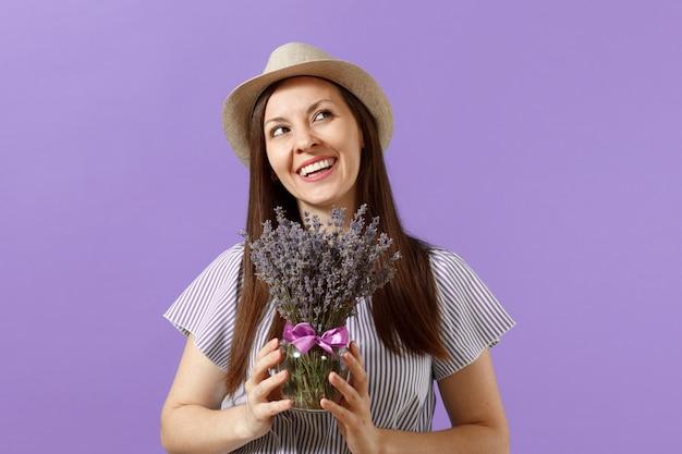 Portrait d'une jeune femme tendre et heureuse en robe bleue chapeau de paille tenant un bouquet de belles fleurs de lavande violettes isolées sur fond violet tendance lumineux. concept de vacances de la journée internationale de la femme