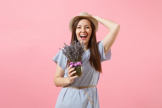 Portrait d'une jeune femme tendre et heureuse en robe bleue, chapeau tenant un bouquet de belles fleurs de lavande violettes isolées sur fond rose tendance vif. concept de vacances de la journée internationale de la femme.