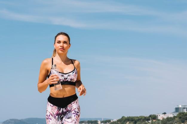 Portrait, jeune, femme, tenue, bouteille eau, dans, main, jogging