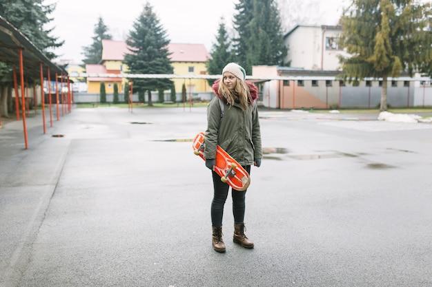 Portrait, de, jeune femme, tenue, skateboard, debout, dans, les, parc