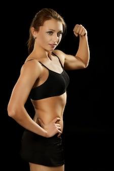 Portrait de jeune femme en tenue de sport sur fond noir