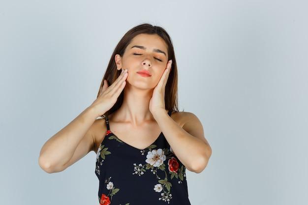 Portrait de jeune femme touchant la peau du visage sur ses joues en blouse et à la vue de face détendue