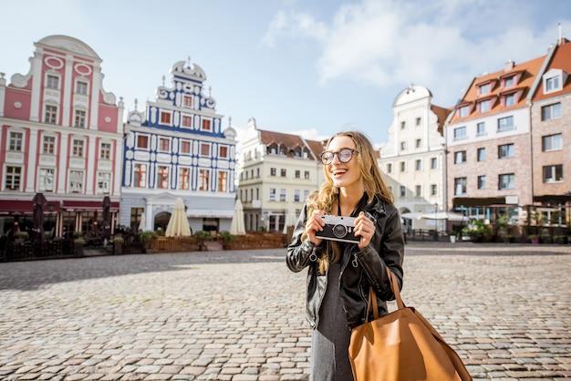 Portrait d'une jeune femme touriste debout sur la place du vieux marché dans la ville de szczecin en pologne