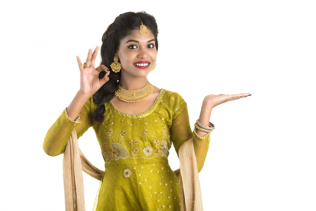 Portrait de jeune femme traditionnelle indienne joyeuse présentant quelque chose, montrant l'espace de copie sur sa paume sur un mur blanc