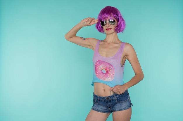 Portrait de jeune femme transgenre avec des problèmes de peau en perruque rose et lunettes de soleil en forme de coeur sur fond bleu