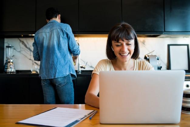 Portrait de jeune femme travaillant avec un ordinateur portable à la maison tandis que l'homme cuisine de nettoyage