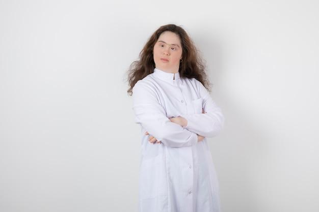 Portrait d'une jeune femme trisomique debout, les bras croisés.