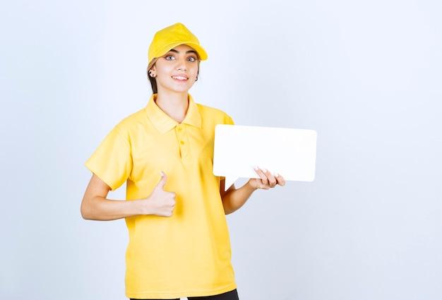 Portrait d'une jeune femme en uniforme jaune avec une bulle vide montrant un pouce vers le haut.