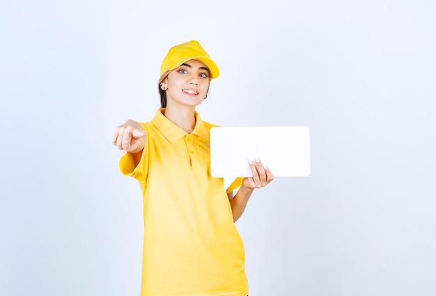 Portrait d'une jeune femme en uniforme jaune avec une bulle vide pointant vers la caméra.