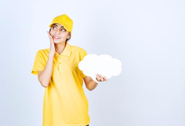 Portrait d'une jeune femme en uniforme jaune tenant un nuage de bulle de dialogue blanc vide.