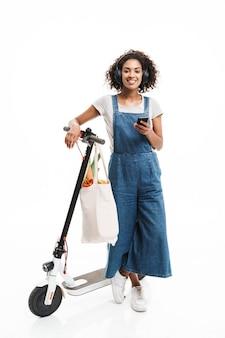 Portrait de jeune femme utilisant des écouteurs et un téléphone portable en roulant sur un scooter avec un sac de nourriture isolé sur un mur blanc