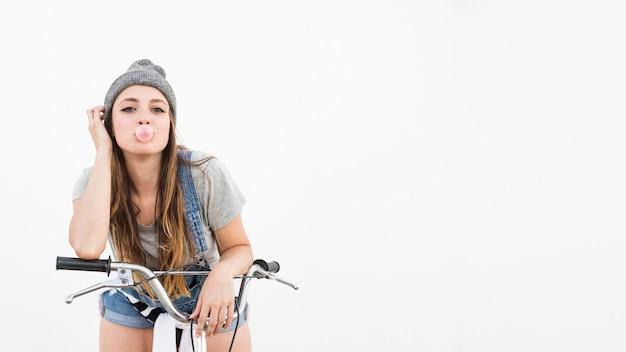 Portrait d'une jeune femme à vélo soufflant des bulles sur fond blanc