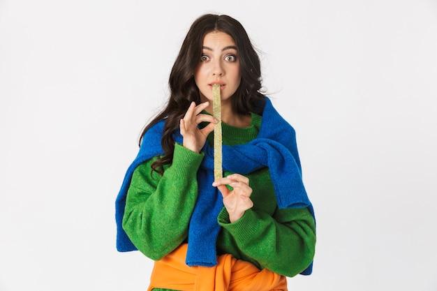 Portrait de jeune femme en vêtements colorés à mâcher de la gomme longue, debout isolé sur blanc