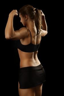 Portrait de jeune femme en vêtements de sport montre des biceps, vue arrière