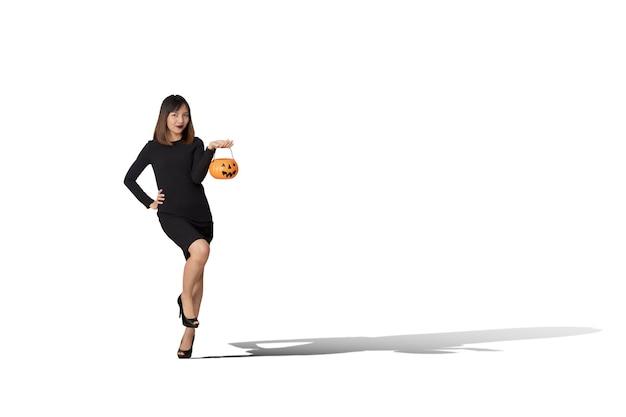 Portrait d'une jeune femme vêtue d'un costume de sorcière noire tient une citrouille pour une fête d'halloween heureuse.