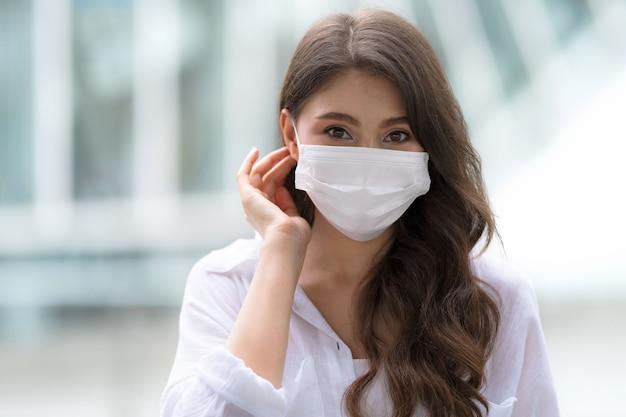 Portrait de jeune femme avec visage souriant portant un masque facial promenades de protection dans une ville