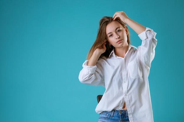 Portrait d'une jeune femme avec un visage triste dans une chemise blanche sur un mur bleu