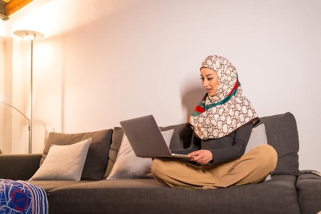 Portrait d'une jeune femme avec un voile blanc sur son ordinateur personnel sur son canapé du salon, faisant un appel vidéo