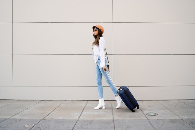 Portrait de jeune femme voyageur portant une valise en marchant à l'extérieur dans la rue. notion de tourisme.