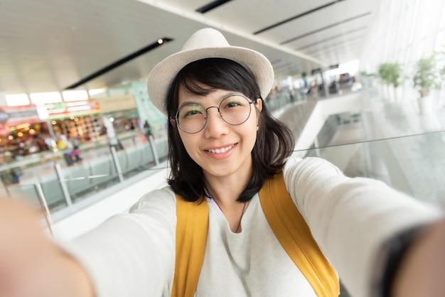 Portrait de jeune femme voyageur porter des lunettes et un chapeau prenant selfie.