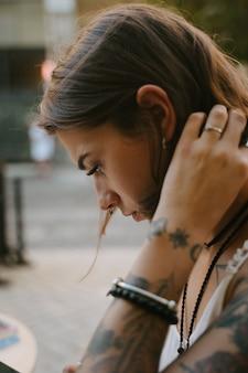 Portrait de jeune femme vue de côté dans la rue, regardant vers le bas