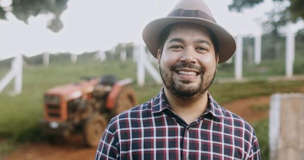 Portrait de jeune fermier latin dans la chemise décontractée à la ferme sur le fond de la ferme.