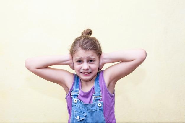 Portrait de jeune fille de 8 ans sur un mur jaune, effrayé couvrant ses oreilles avec ses mains