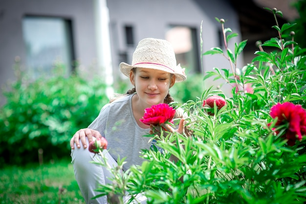 Portrait d'une jeune fille adolescente dans un chapeau de paille dans un jardin d'été en fleurs