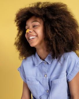 Portrait de jeune fille adorable posant avec des autocollants emoji sur son visage