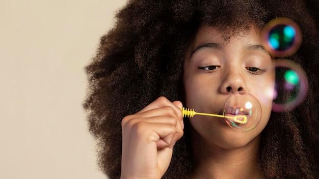 Portrait de jeune fille adorable posant en jouant avec des bulles de savon