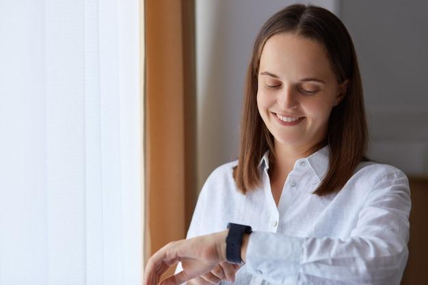 Portrait d'une jeune fille adulte souriante vêtue d'une chemise blanche regardant sa montre-bracelet avec une expression heureuse, posant dans une pièce lumineuse près de la fenêtre, utilisant une montre intelligente avec plaisir.