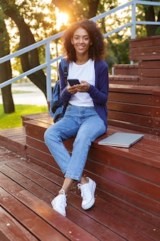 Portrait d'une jeune fille africaine heureuse avec sac à dos à l'aide de téléphone mobile tout en se reposant dans le parc