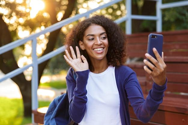 Portrait d'une jeune fille africaine joyeuse avec sac à dos au repos dans le parc, prenant un selfie, agitant la main