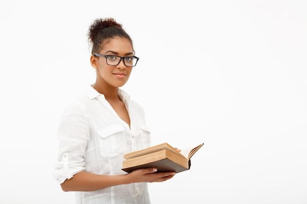 Portrait de jeune fille africaine avec livre sur mur blanc