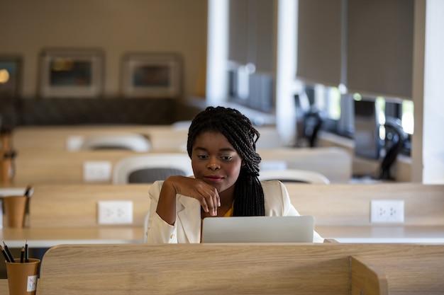 Portrait d'une jeune fille africaine travaillant sur un ordinateur portable dans un café pendant une pause-café une pause détente