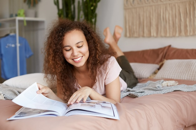Portrait de jeune fille afro-américaine joyeuse reposée aux cheveux bouclés, se trouve sur le lit et lit un nouveau numéro du magazine préféré, profitez de la journée, sourit largement et a l'air heureux.